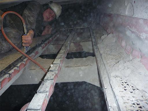 operatør i pukkverk bruker trykkluft til å rengjøre siktemaskin